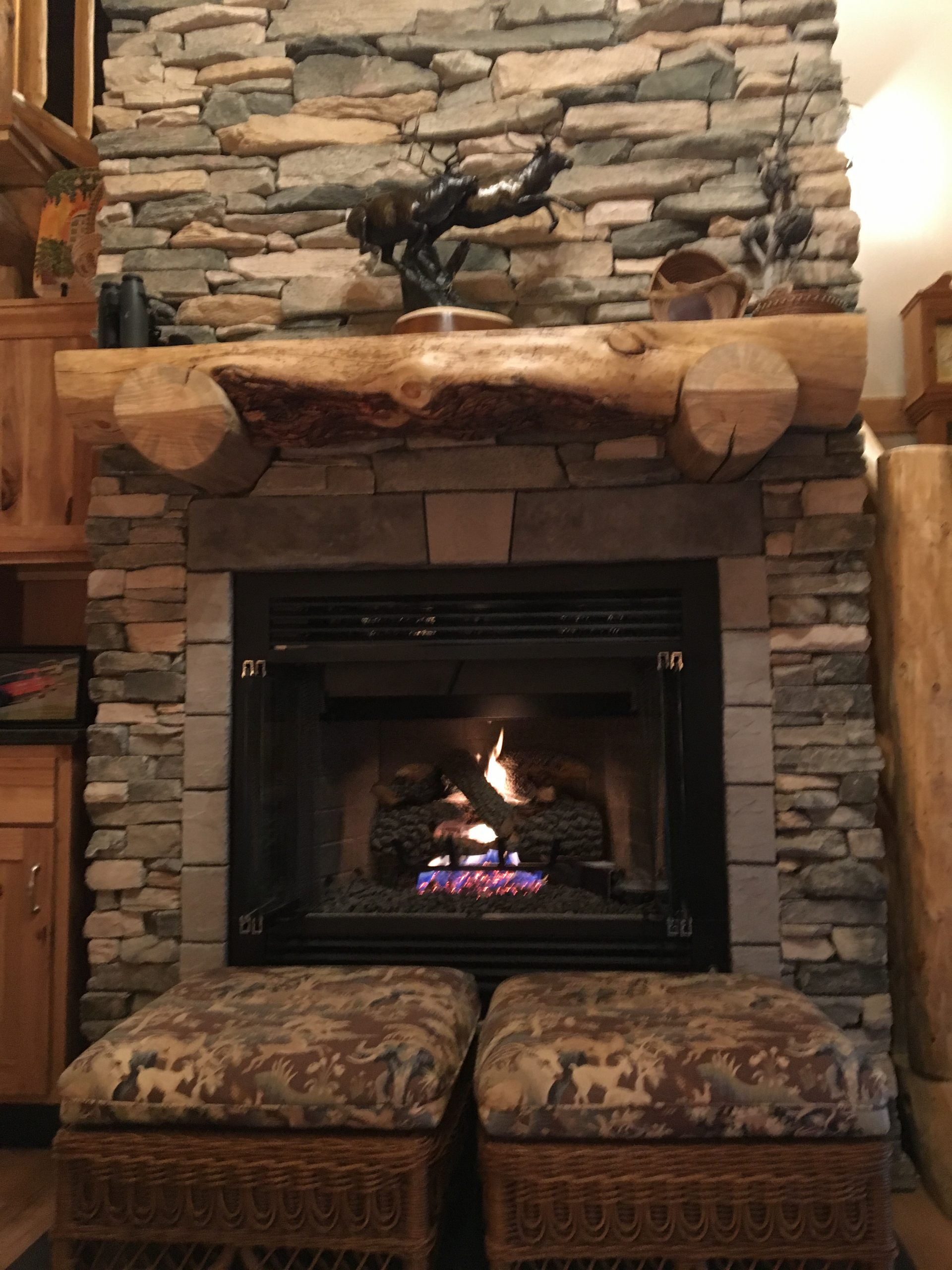A handcrafted log mantle and stacked stone make a beautiful focal point in this log homes' great room.