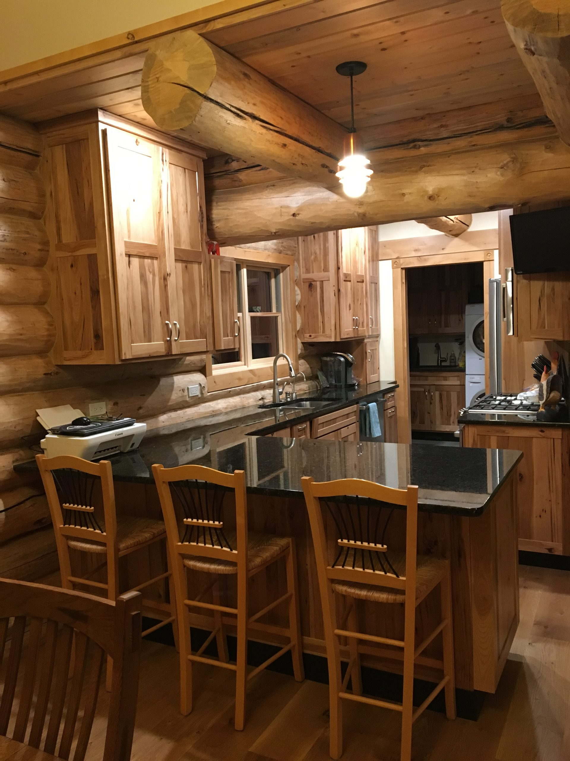 A small but efficient kitchen has custom cabinets and granite counter tops in this log home.