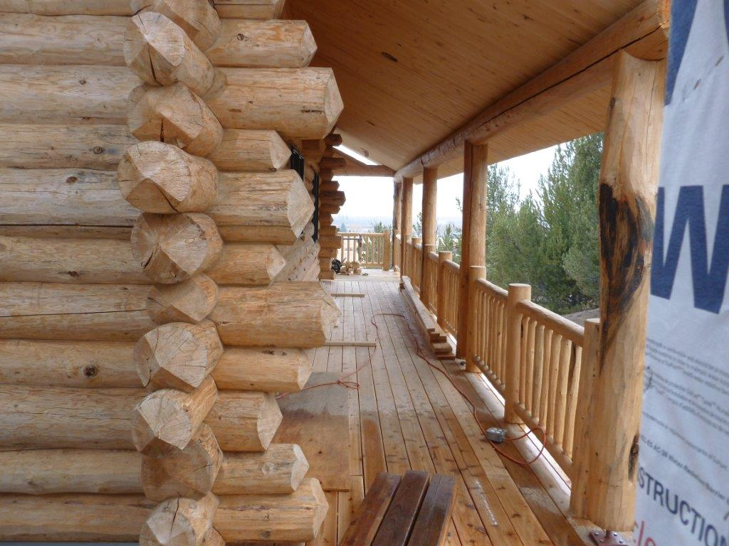 Work is underway on the covered porch of this Scandinavian full scribe log home.