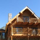 Close up of log home balconies with log railings on gable end of custom log home.