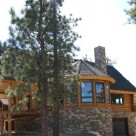 Exterior of handcrafted log home with large covered entry framed with log truss, octagon sunroom and stone chimney set on stone faced basement on hillside in California