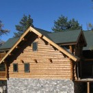 End view of handcrafted log home with full log gable end and log dormers set on stone foundation.