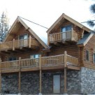 Exterior side view of handcrafted log home with two dormers with balconies set above large deck with log rails on stone covered lower level.