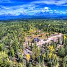 Spectacular aerial view of Montana Log Home set in forest with mountains of Glacier National Park.