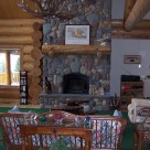 Cozy couch in front of custom river rock fireplace with log mantle in handcrafted Cedar log home.