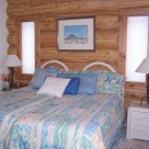 King size bed with white nightstands against handcrafted cedar log wall.