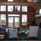 Great room of Cedar log home with river rock fireplace and glass wall with views to Montana forest.