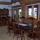Oak dining table and chairs and classic oak china hutch in cedar log home with glass dorrs viewing out to deck with log rails.