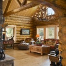 Interior great room of handcrafted log home with log truss and round top windows.