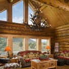 Interior living room of log home with glass wall.