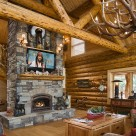 Interior living room of handcrafted log home with stone fireplace and diamond log truss