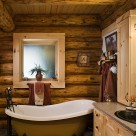 Clawfoot tub in bathroom of handcrafted log home