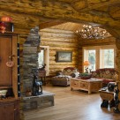 Living room of custom log home viewed through log archway. Stone fireplace and antler chandelier.