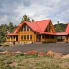 Exterior log home with red metal roof