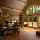 Great room of custom log home with view of forest through round top windows.