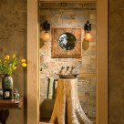 Flare base cedar stump with copper sink on top with stone wall behind viewed through open door.