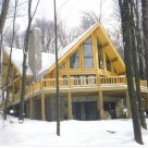 Exterior log home with prow front windows in winter
