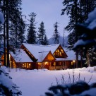Exterior twilight photo of luxury log home in winter with multiple roof lines and transom windows.
