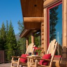 Two custom wood rocking chairs sit on deck in front of custom log home.