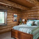 Handcrafted log home bedroom with cozy queen bed on white carpet.