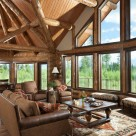 Milled log beams frame large windows with forest views in log home living room.