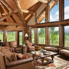 Open living room and dining room with massive glass walls surounded by log posts. Log beams and pine ceilings above in this beautiful room.