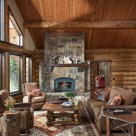 Log home greatroom with stone fireplace beyond cozy seating area. Log staircase leading to open loft with log railings and bear carvings in log posts.