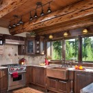 Log home kitchen with dark cabinetry, copper sink and range hood above hardwood flooring.