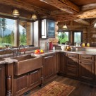 Custom log home kitchen with copper sink surrounded by dark cabinets. 8' window above sink has views to glacier national park.
