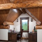 Office desk and chair tucked into gable dormer in loft of custom log home.