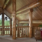 Log posts, ridgepole and purlins support pine ceiling in handcrafted log home.