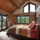Master bedroom with king size bed in handcrafted log home with trapezoid windows in gable end.