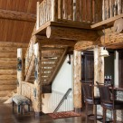Log staircase leading to open loft with log railings.