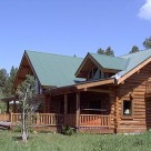 Exterior photo of handcrafted chink style log home with green metal roof, covered porches dormer and balcony with log railing.