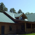 Exterior photo of handcrafted log home with metal roof, covered entry porch and small gable dormer.