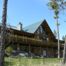 Custom log home with covered porches on walkout basement near Lakeside Montana.
