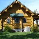 Exterior end view of Cedar log home with log purlins and covered porch.