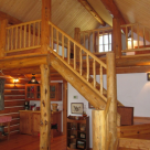 Log staircase with log railings leading to loft of small log cabin