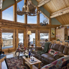 Interior log home living room with prow window wall