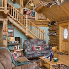 Interior of handcrafted log home with log stairs to loft