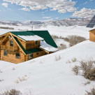Log home with shed dormers in winter