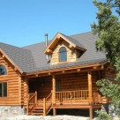 Exterior log cabin with gable dormer, covered porch and log railing