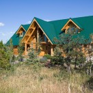 Handcrafted log home with green metal roof with small dormers on each side of center roof supported by log post and beams.