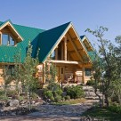 Close up photo of custom log home with green metal roof and welcoming entry way with log truss above.