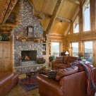 Great room of handcrafted log home with river rock chimney, leather sofa's and a full glass wall with views to the Colorado mountains.