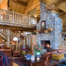 Log home greatroom with massive stone fireplace, cathedral ceilings with catwalk above sided with log railings.