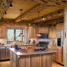 Custom kitchen in handcrafted log home with rustic log post and beams and pine t&g ceiling.