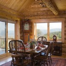 Beautiful dining table and chairs set on area rug in handcrafted log home with wood floors and large windows with views to forest beyond.
