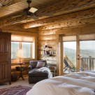Master bedroom with custom armoire in handcrafted log home with french doors showing views to Colorado mountains from cozy queen bed.