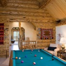 Pool table in loft of custom log home with skip peeled logs, exposed beam ceiling with pine ceiling.